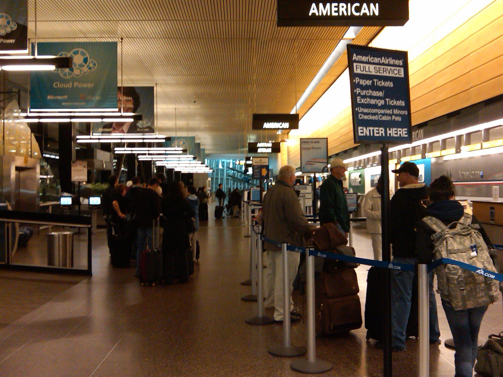 line of 50+ travelers at airport ticket counter with no agents available