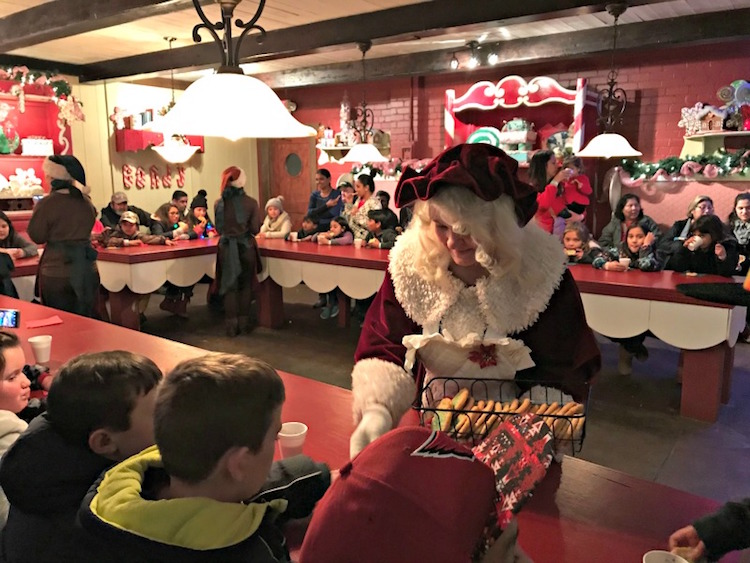 Mrs. Claus passing out cookies during a stop at her bakery in Santa's Workshop during the North Pole Experience.