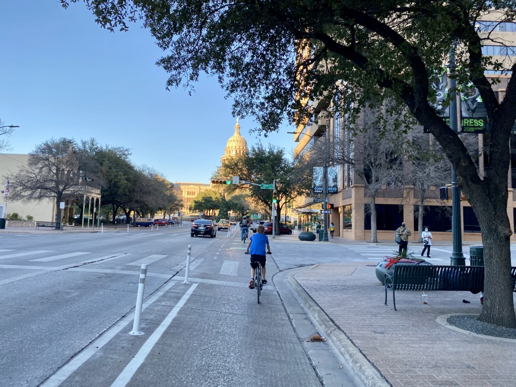 Biking toward the Texas State Capitol on a weekend itinerary in Austin Texas.