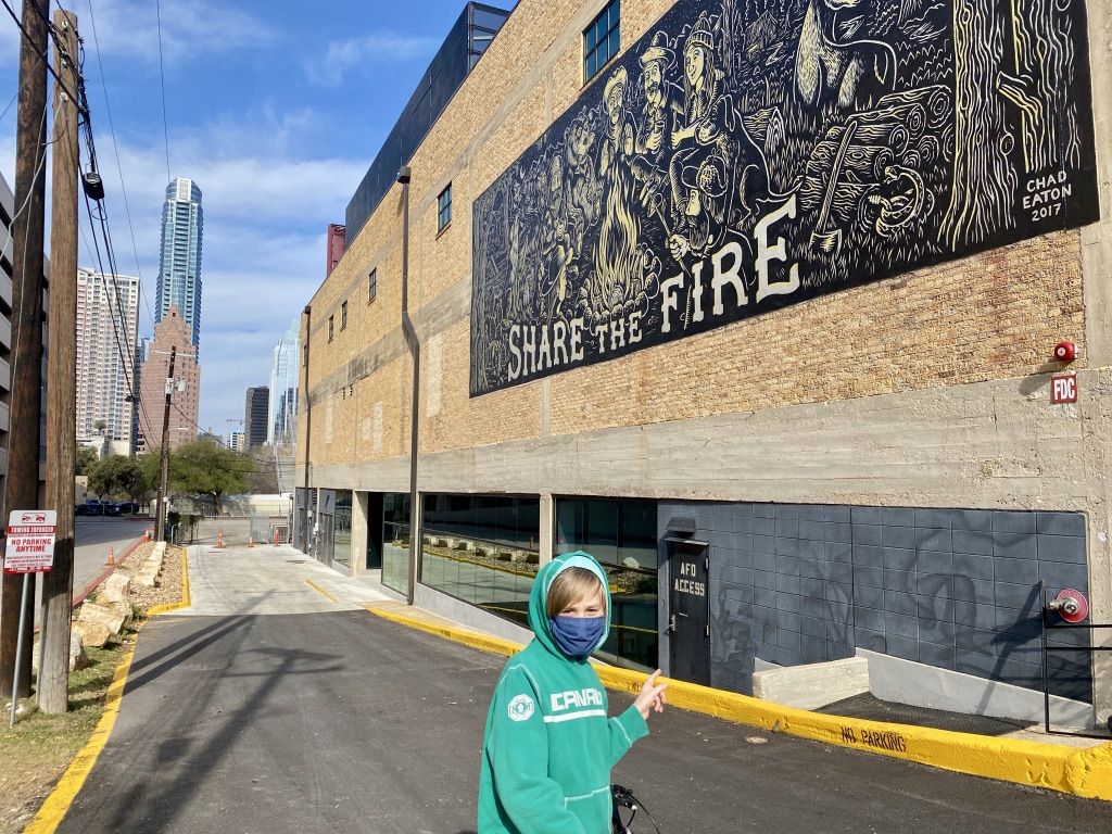 A girl looks at a mural in Austin Texas