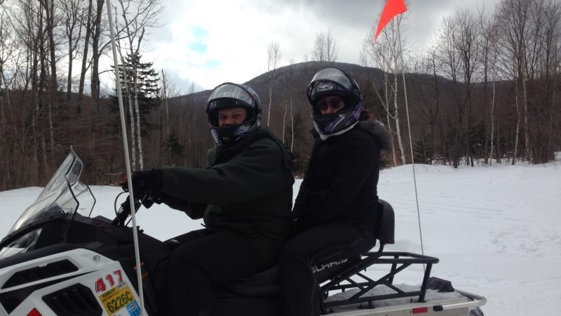 Husband and wife on a snowmobile together in Stowe Vermont. They are in full snow gear and helmets. There are mountains in the background.