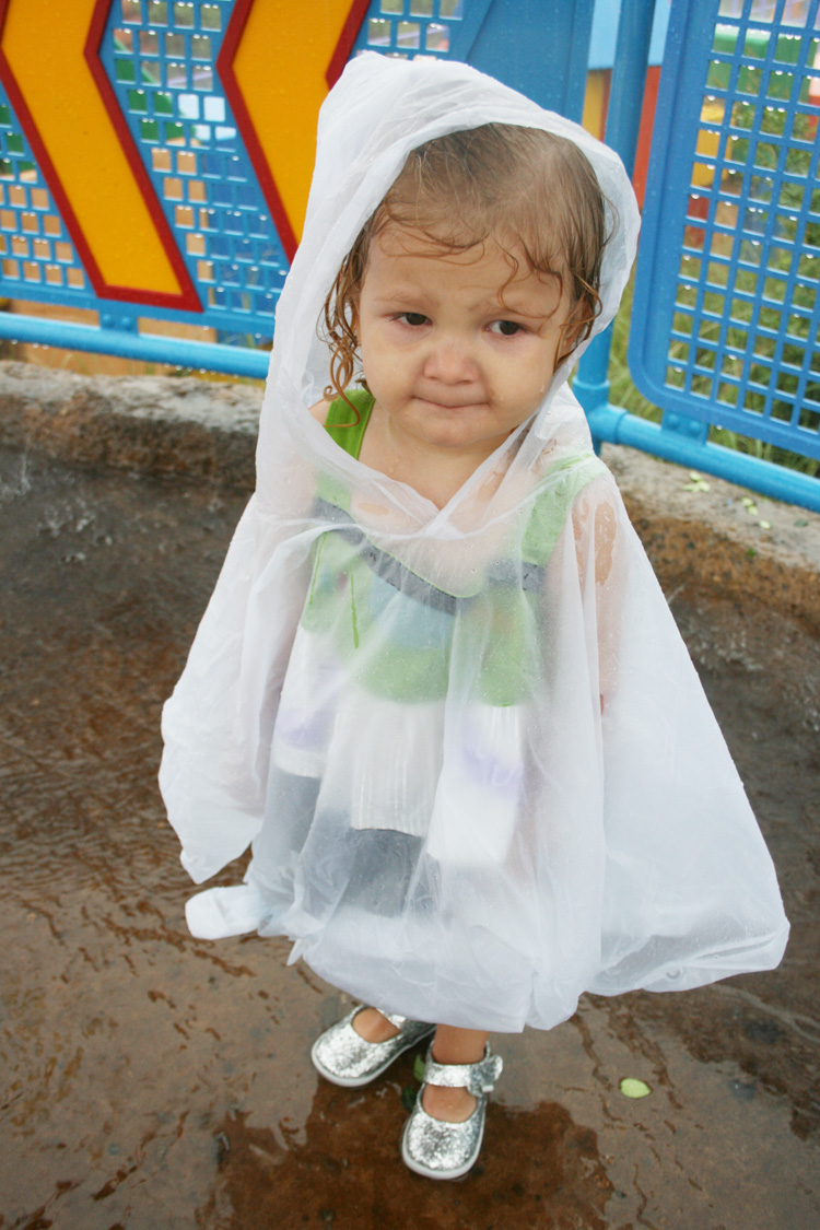 Toddler in poncho at Disney World in the rain - TravelingMom