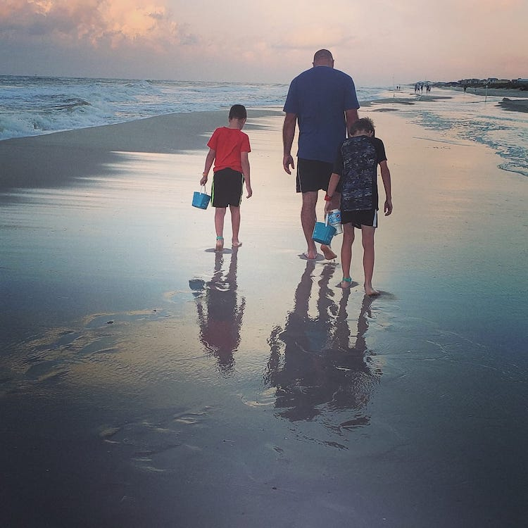 father and sons collecting seashells at sunset on the beach