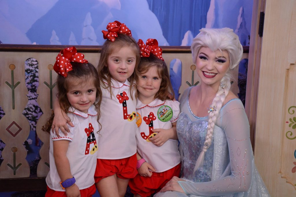 Girls posing with Princess Elsa at Disney World - TravelingMom