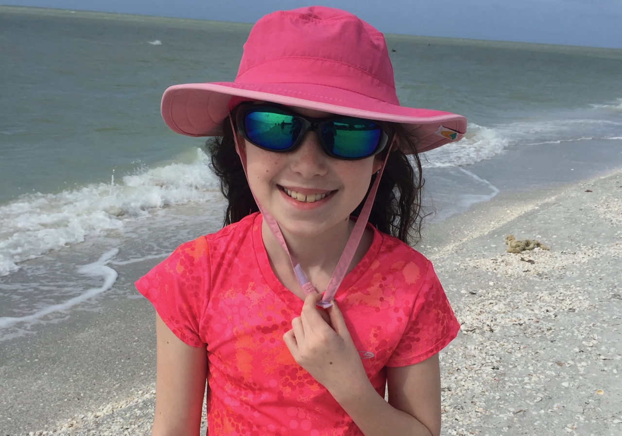 girl in a sunhat at the beach - TravelingMom