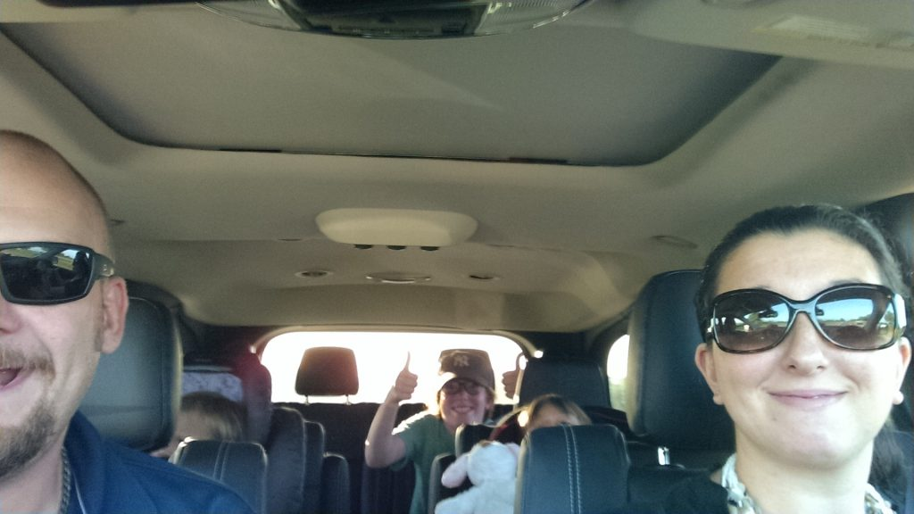 Family in a minivan driving to a destination - TravelingMom
