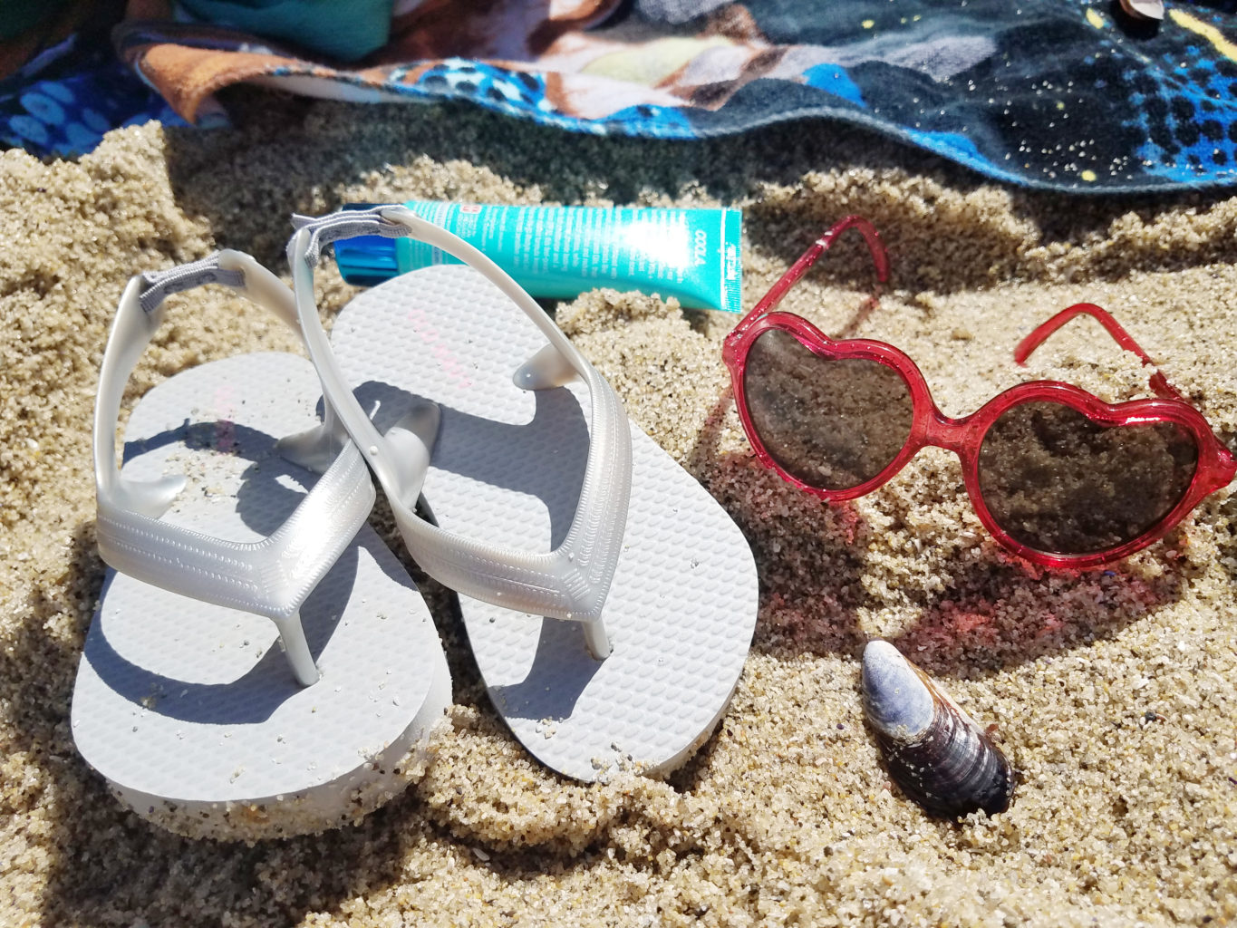 Toddler flip flops and sunglasses with sunscreen and a shell on the beach