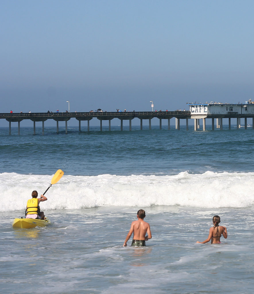 Kayak and swimmers in Ocean Beach with pier in the background
