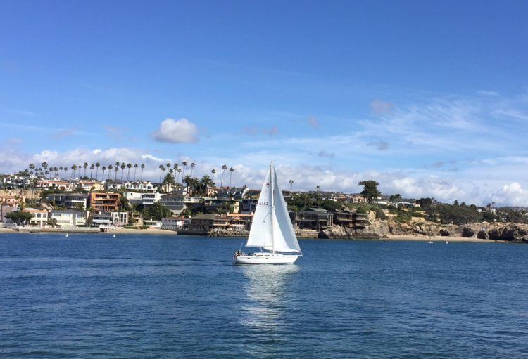 A sailboat glides through Newport Harbor in Orange County.