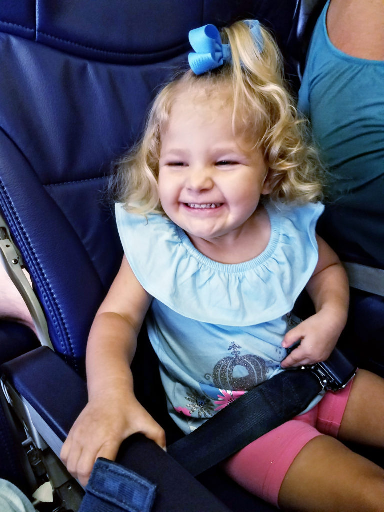 Happy toddler girl on an airplane - TravelingMom