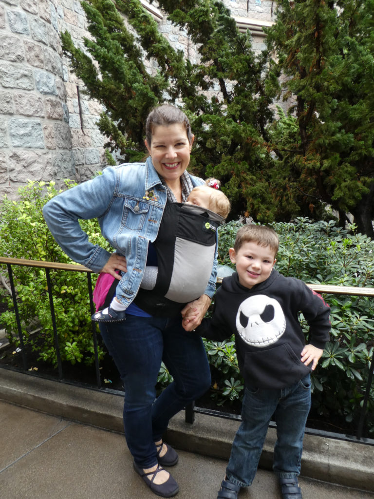Mom with baby in a baby carrier and son at Disney World - TravelingMom