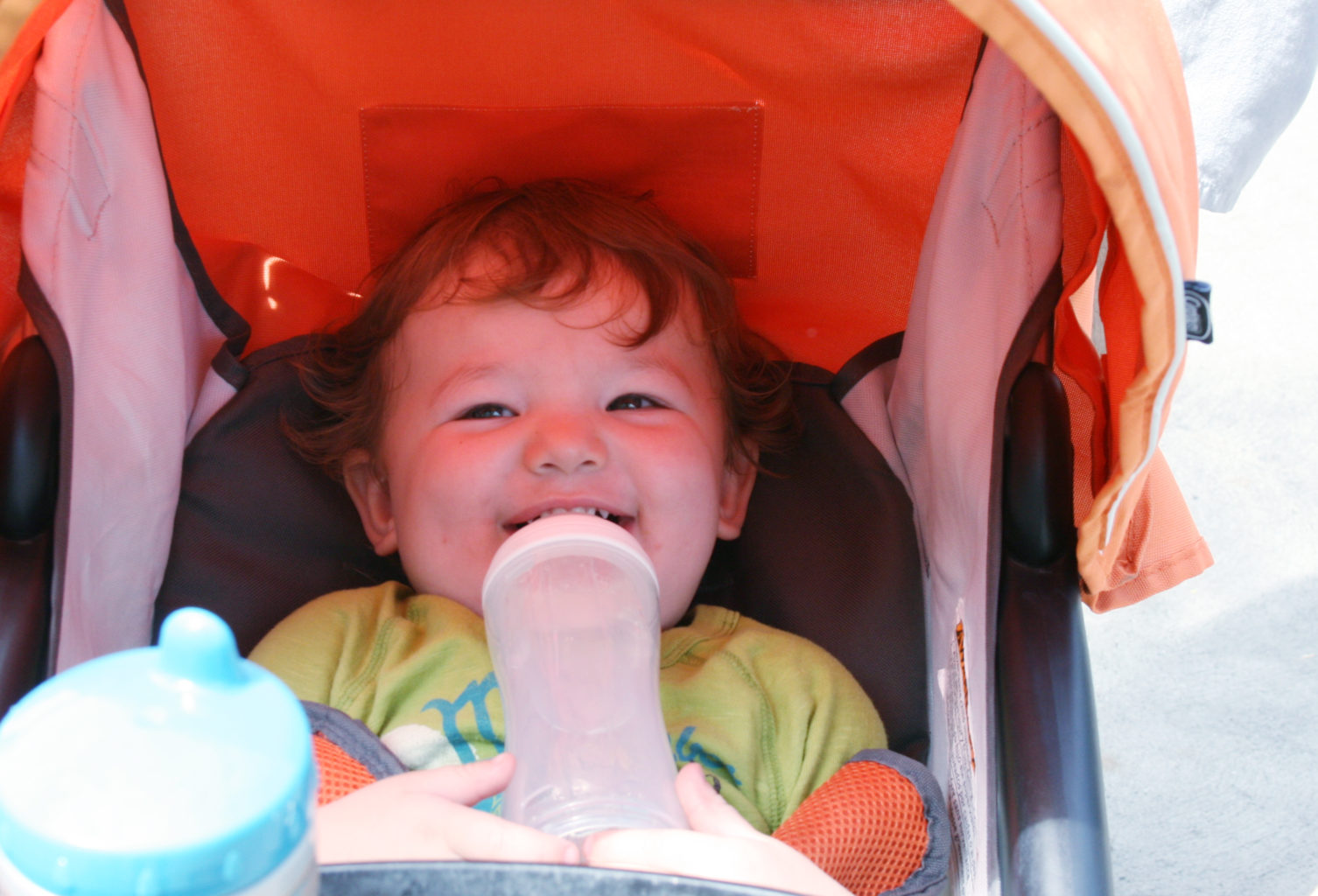 Happy baby in a stroller drinking a bottle - TravelingMom