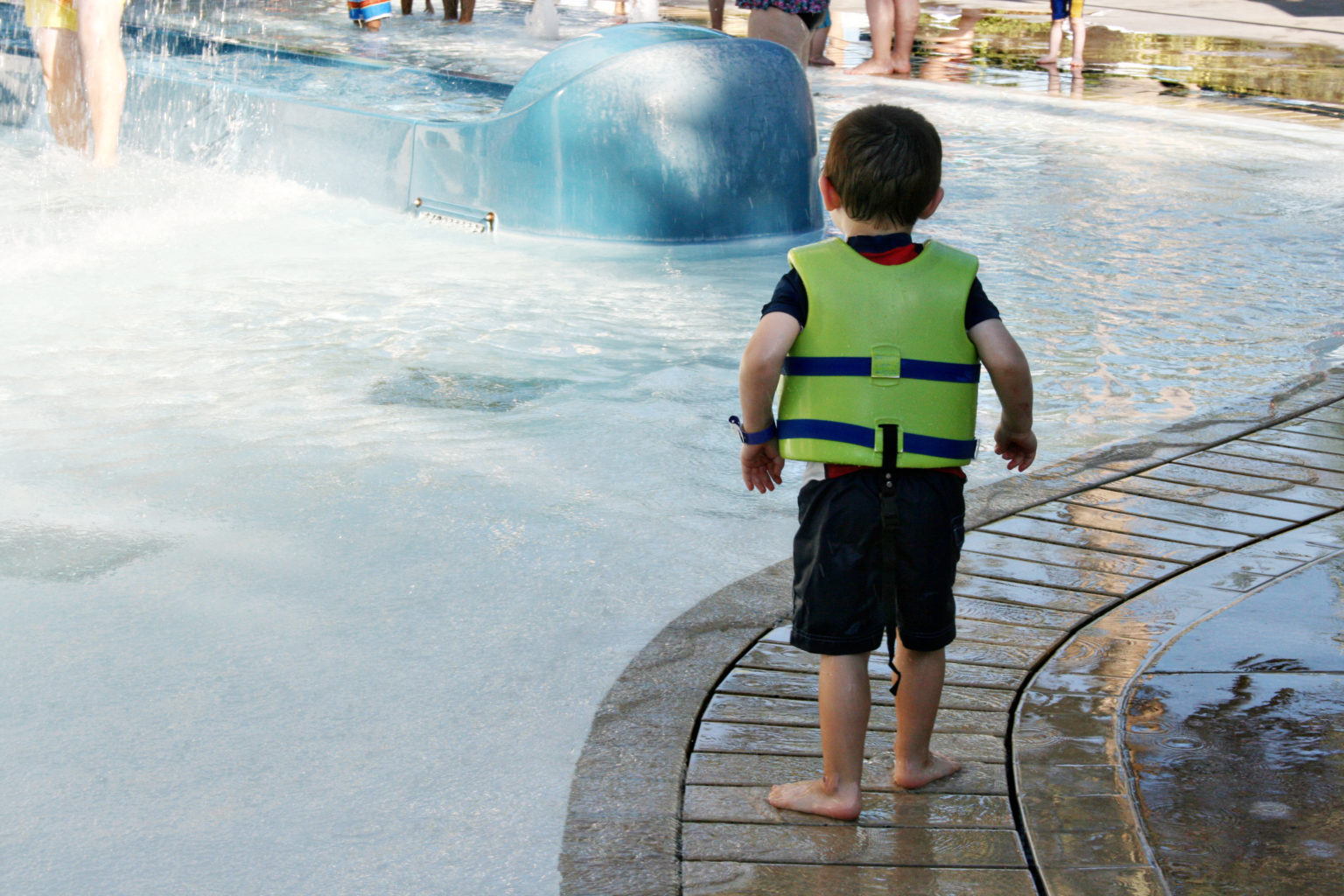 Toddler boy in a life jacket at Disneyland Hotel pool - TravelingMom