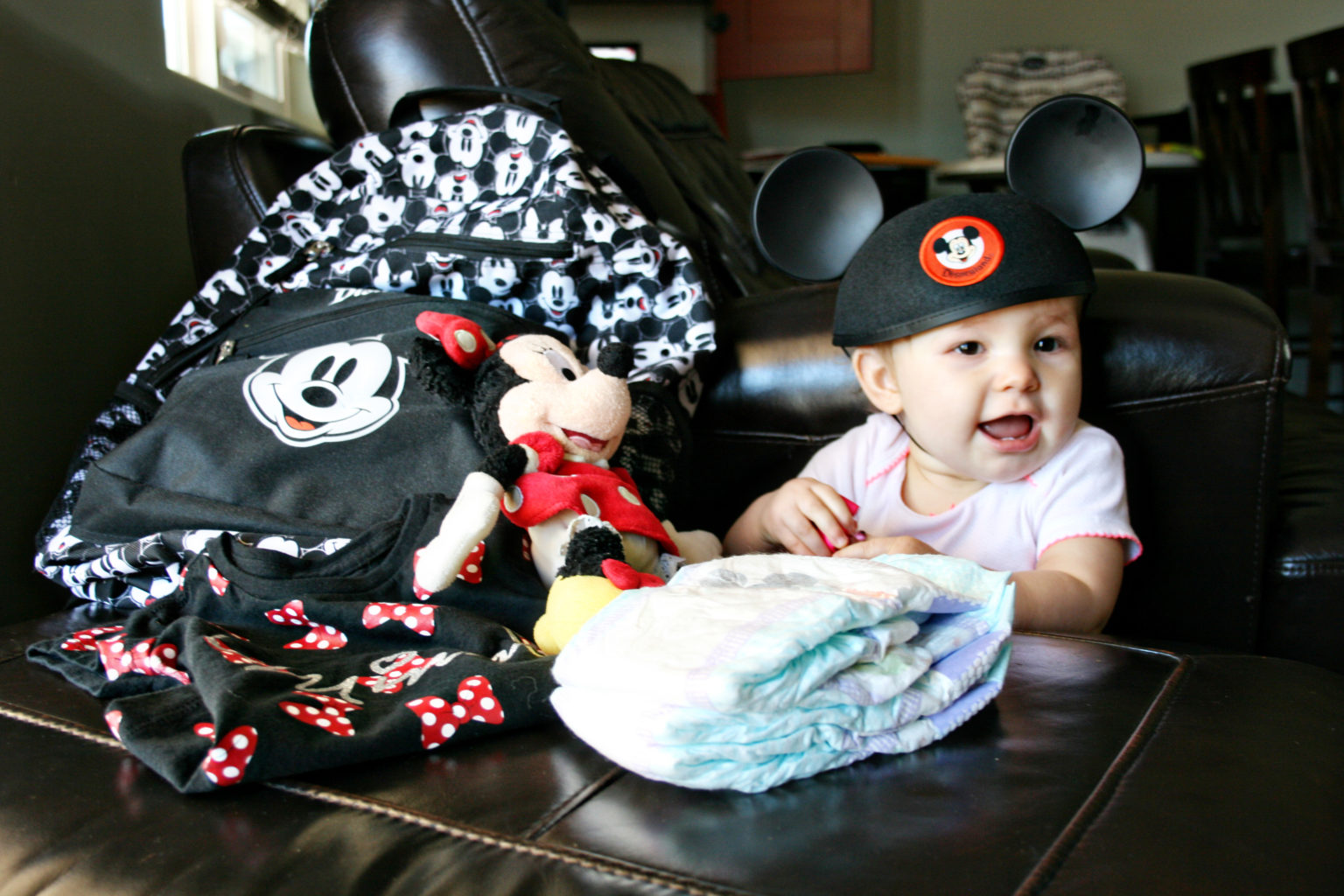 Disney parks travel bag for babies and toddlers with baby wearing Mickey ears - TravelingMom