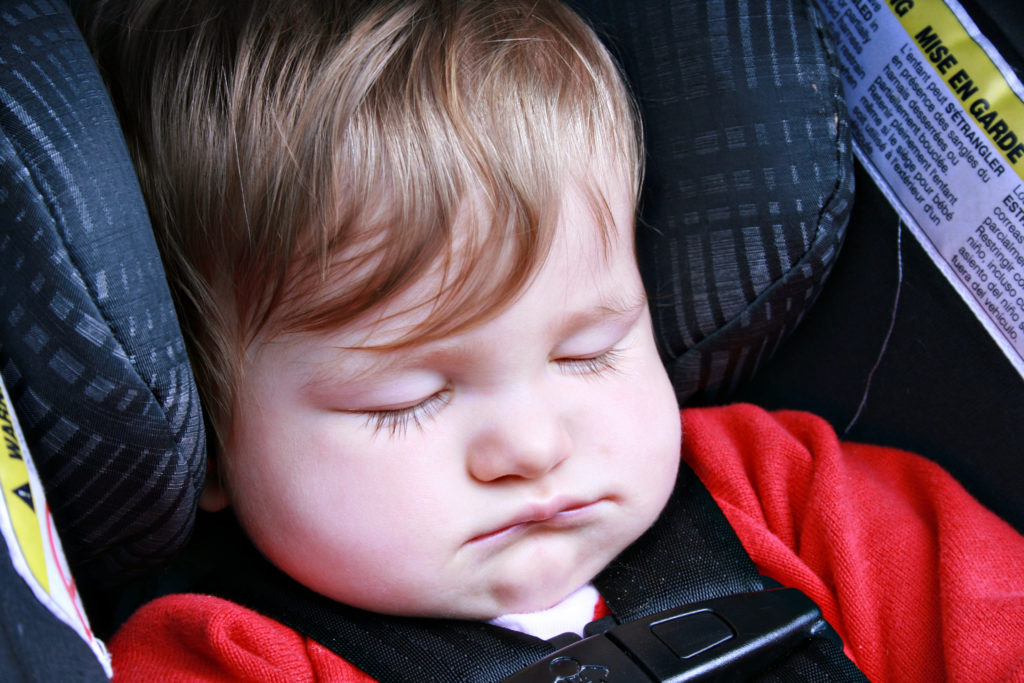 Car seat napping baby on a road trip
