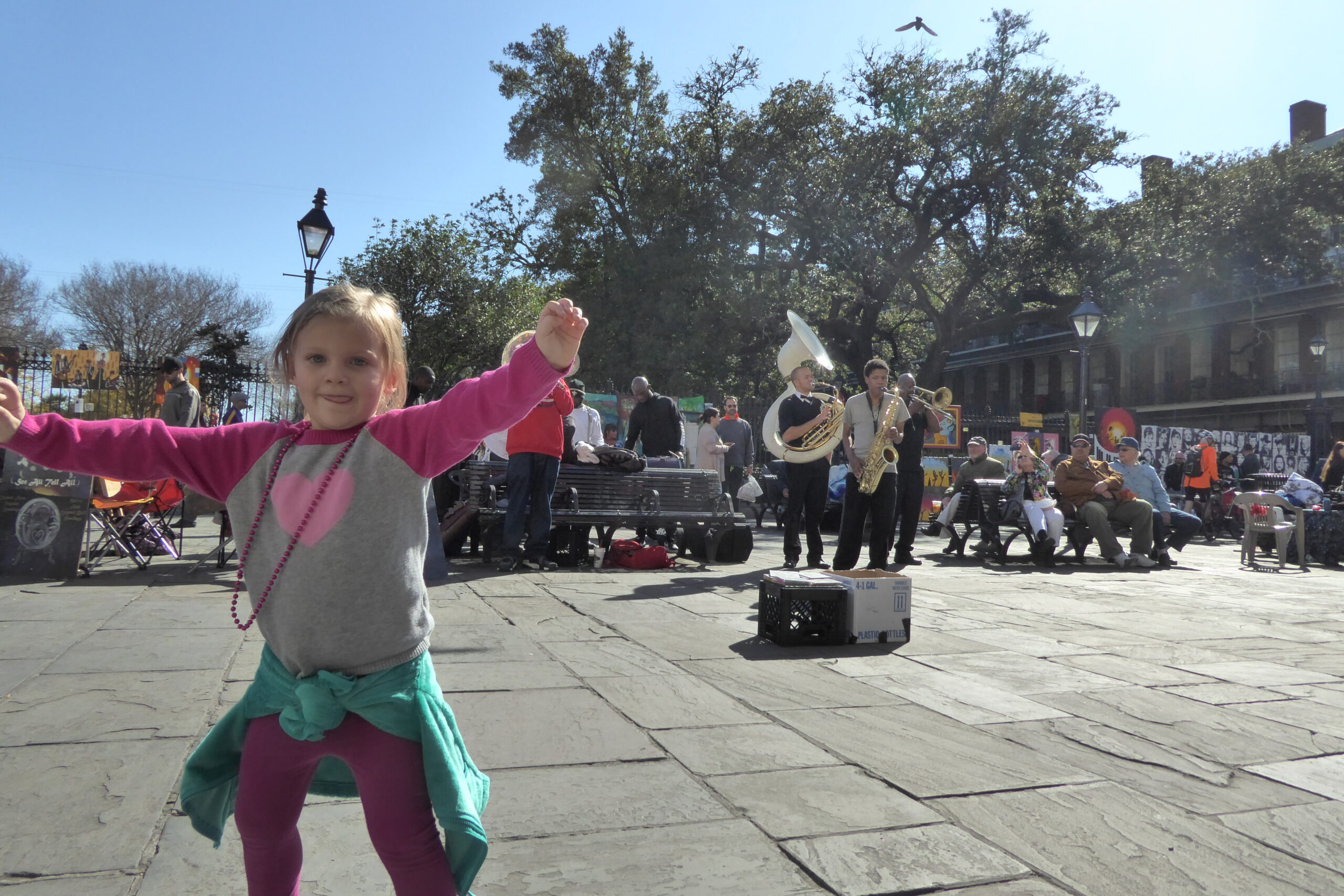 blonde child wearing beads dancing in front of a street band