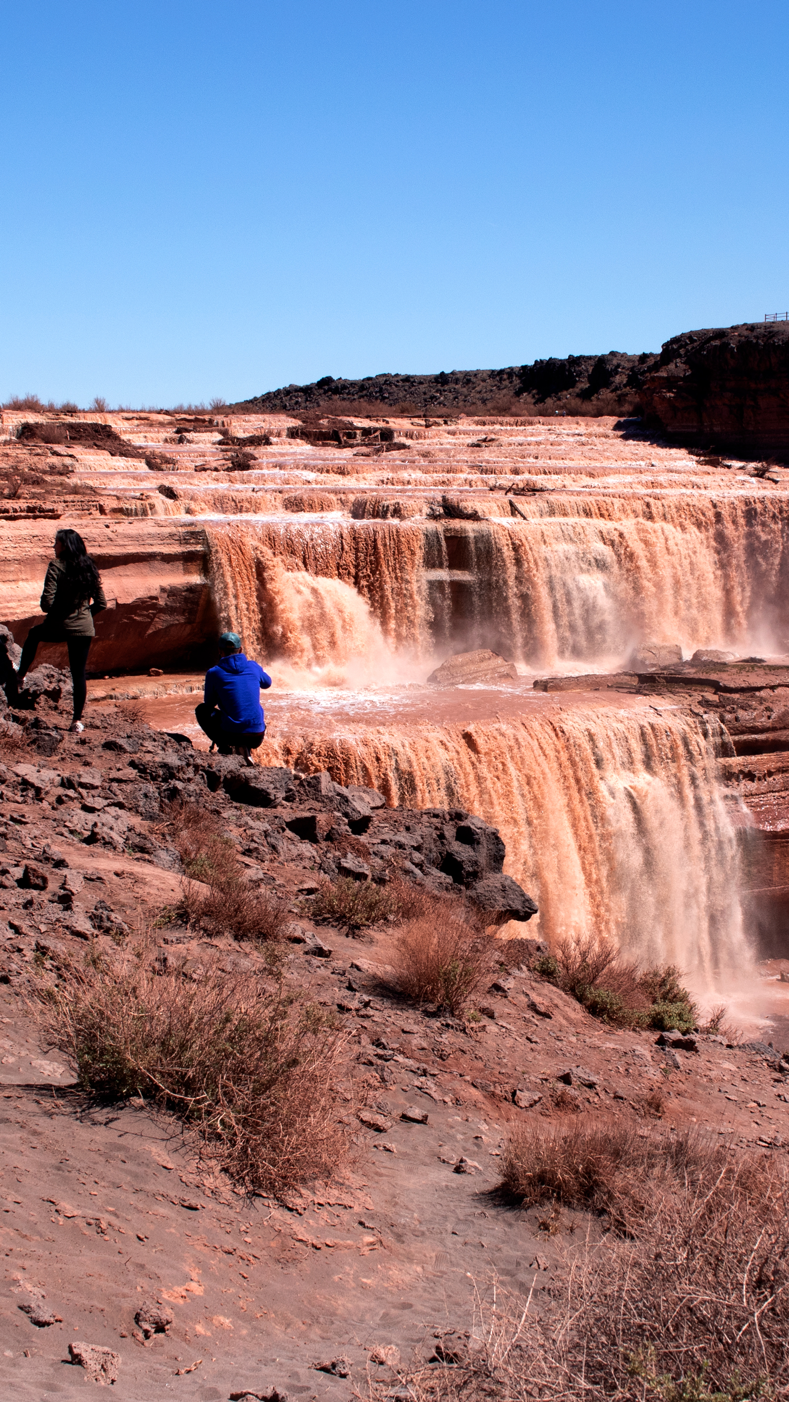 A group of photographers gather near the edge of the canyon wall to set up photos of Grand Falls AZ.