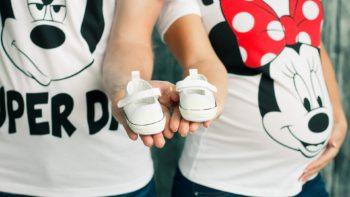 Pregnant mom and expecting dad wearing Disney shirts