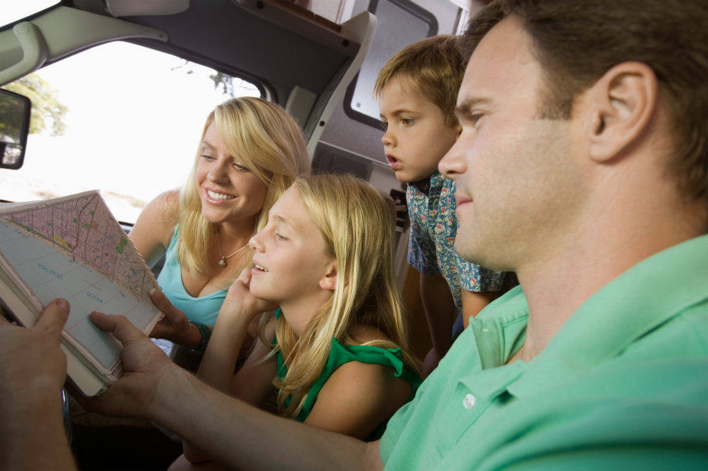family in car looking at a map