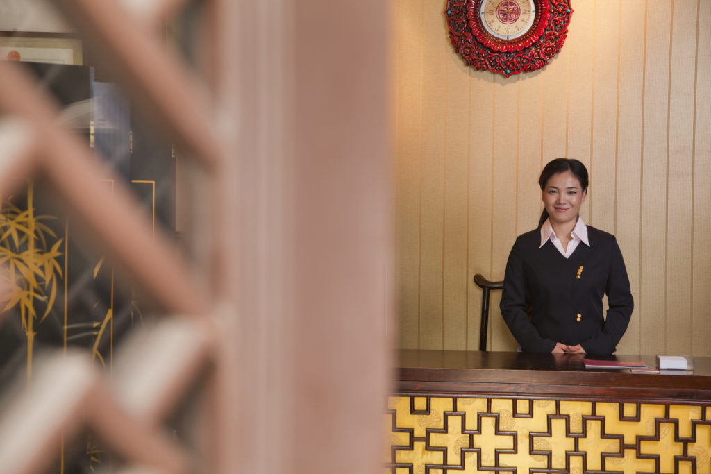 receptionist at hotel front desk greeting hotel business travelers