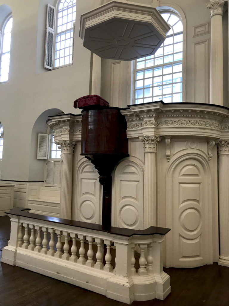 The off-white pulpit of a meeting house is shown. A book is shown perched on a dark wood piece of the pulpit.