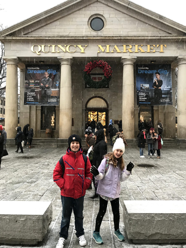"A building with columns and gold lettering that reads ""Quincy Market"" is shown in the background. Two children pose in front. Other people walk around between the children and the building."