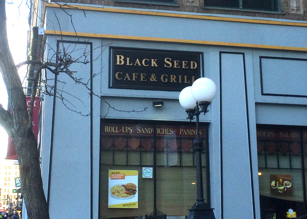 A building is shown from the outside. The storefront has a black sign with gold lettering that says Black Seed Cafe & Grill.
