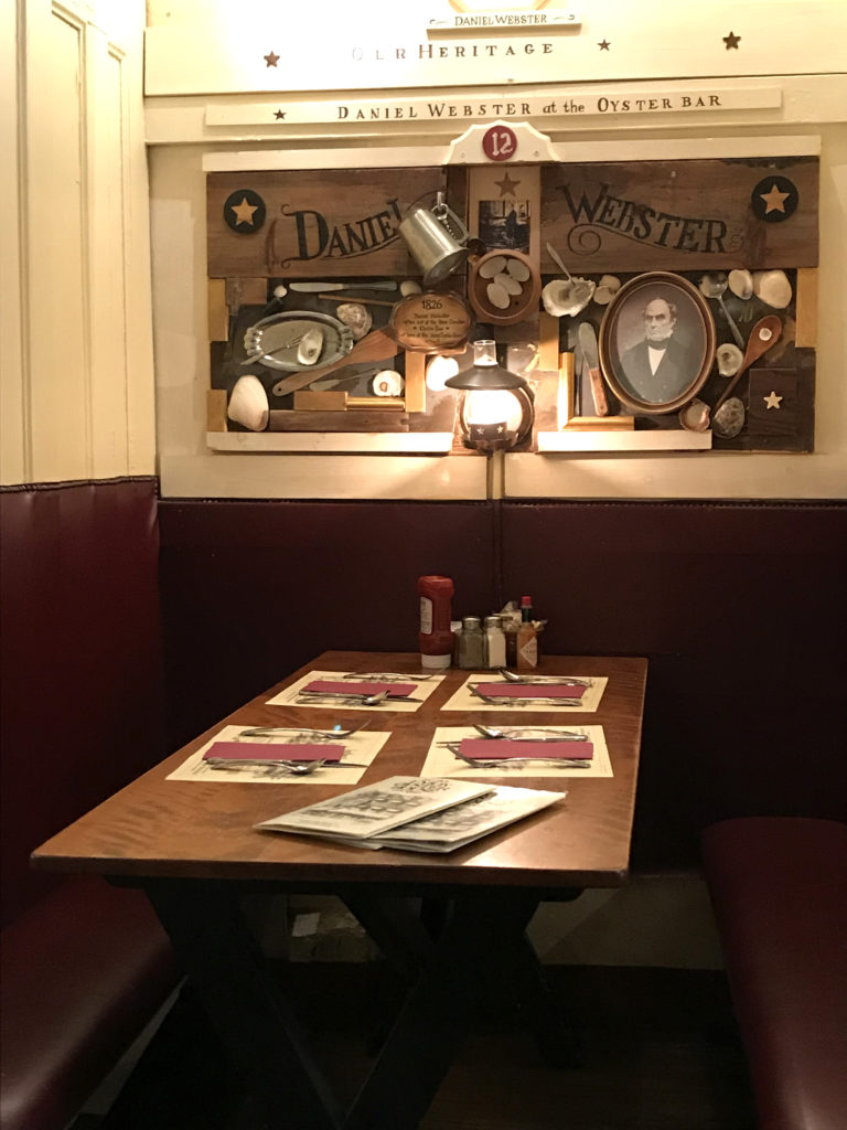 A booth at Union Oyster House is shown with a medium colored brown wood table, dark red seating and an homage to Daniel Webster.