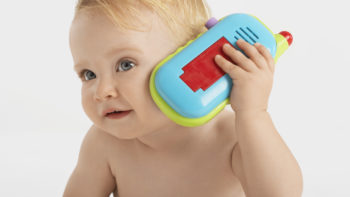 Baby on pretend cell phone.