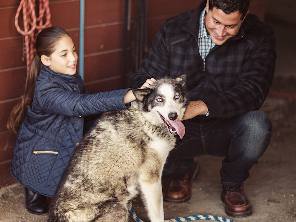Try new activities on an all inclusive family vacation like father and daughter with sled dogs