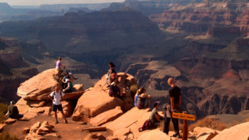 A group of people are sitting perched on the edge of rocks at the edge of the Grand Canyon