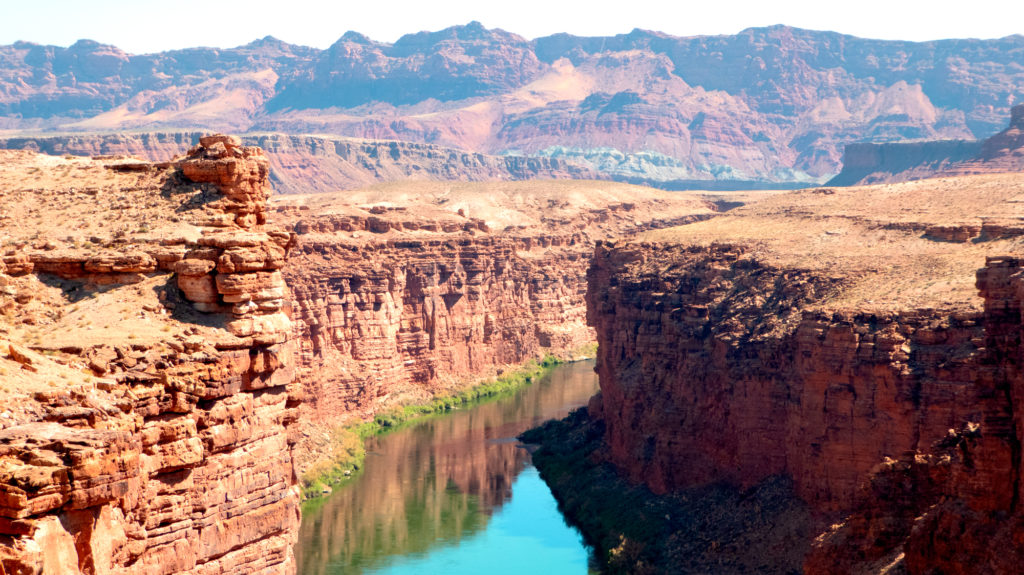 A gently flowing Colorado River between the steep walls of Marble Canyon.