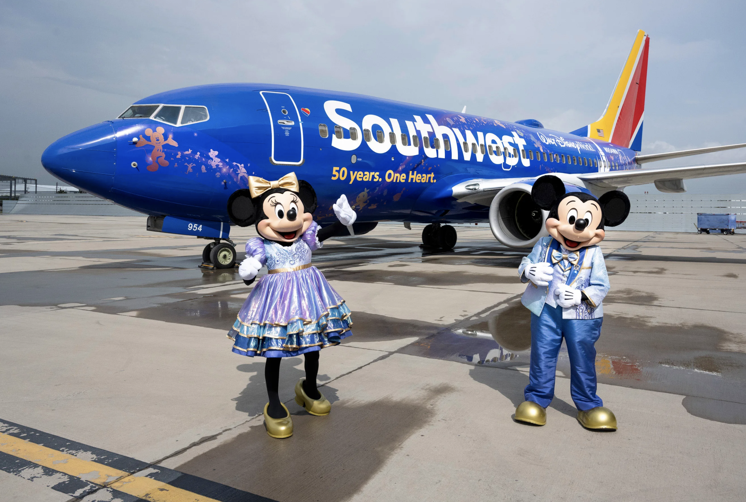 mickey and minnie standing in front of southwest airplane