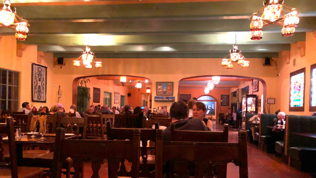 Picture of a restaurant dining room with antique Native American art on the walls.