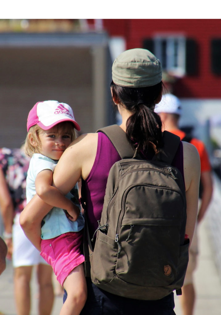 mom with back to camera wearing backpack and holding daughter