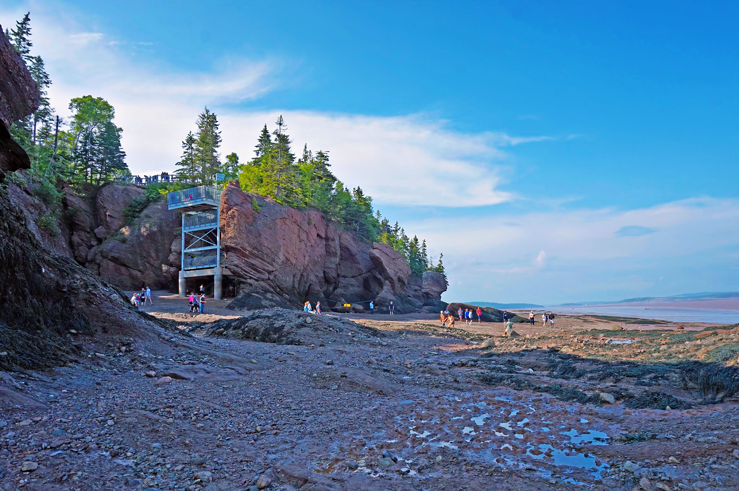 Bay of Fundy. People are enjoying their time walking on the ocean floor at the Hopewell Rocks in New Brunswick.
