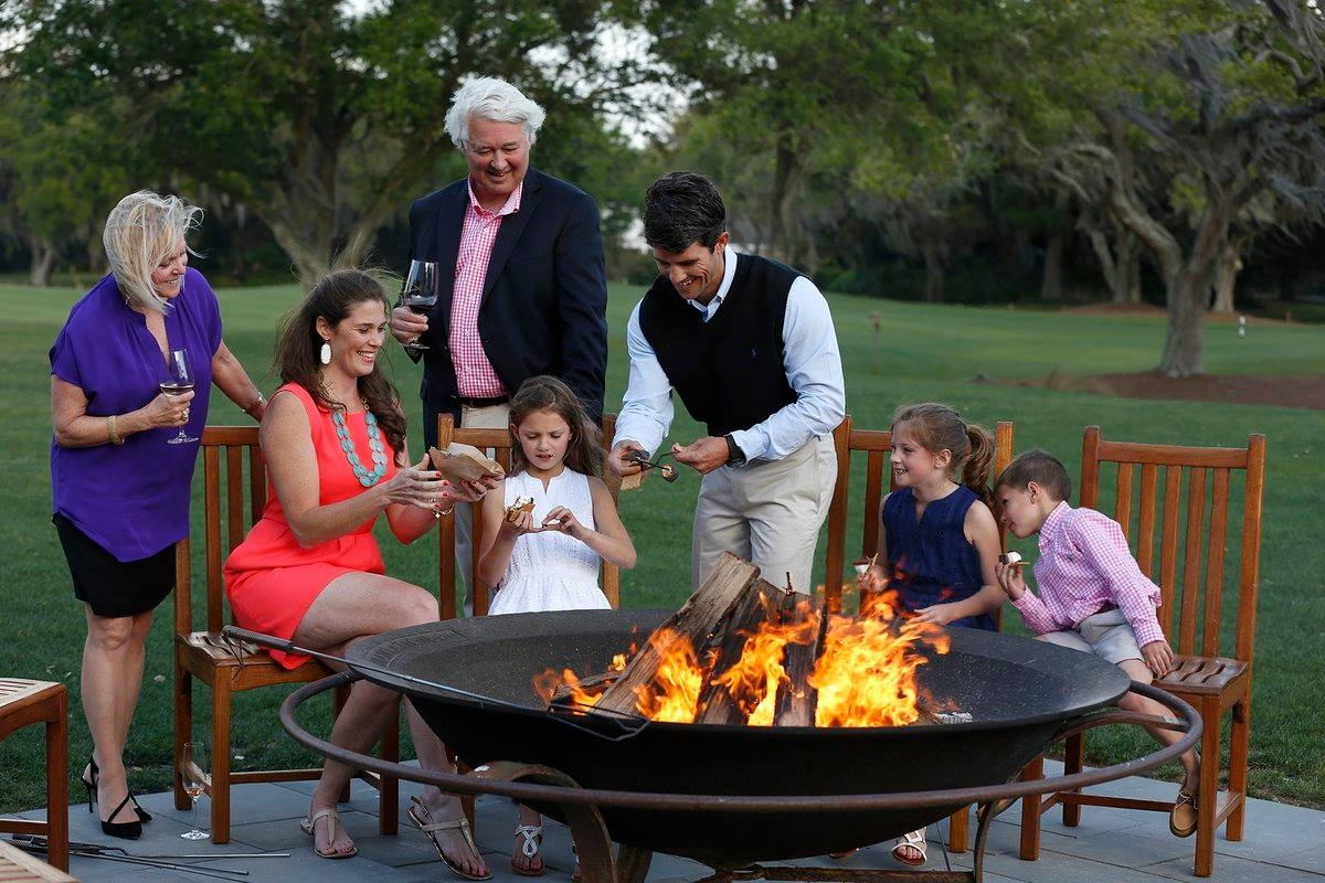Family celebrating Thanksgiving around the campfire at Sea Island GA Resort - TravelingMom