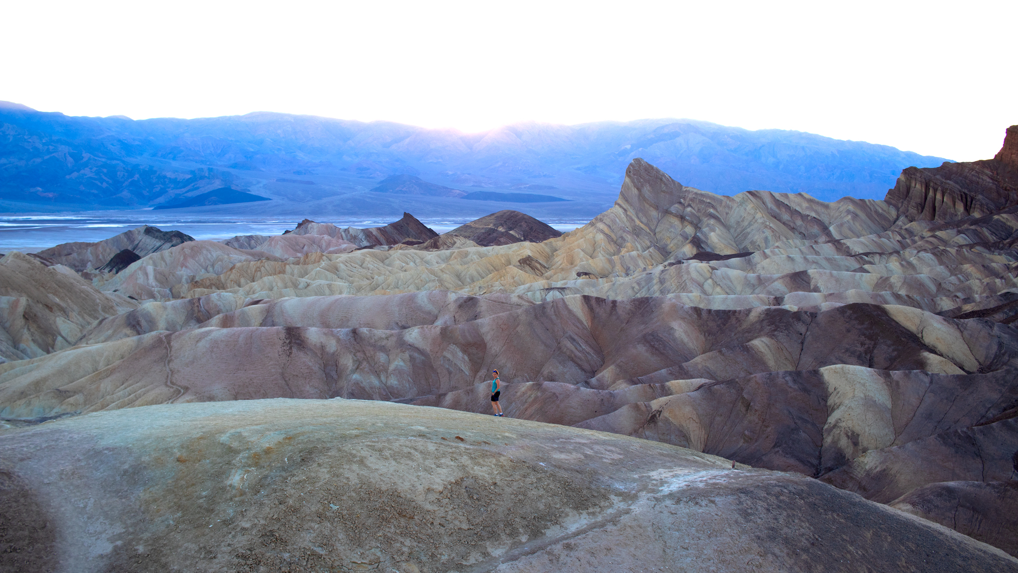 A lone hiker walk across the badlands at Zabriskie Point