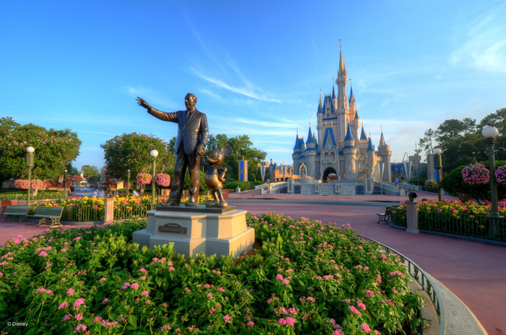disney statue and castle at magic kingdom