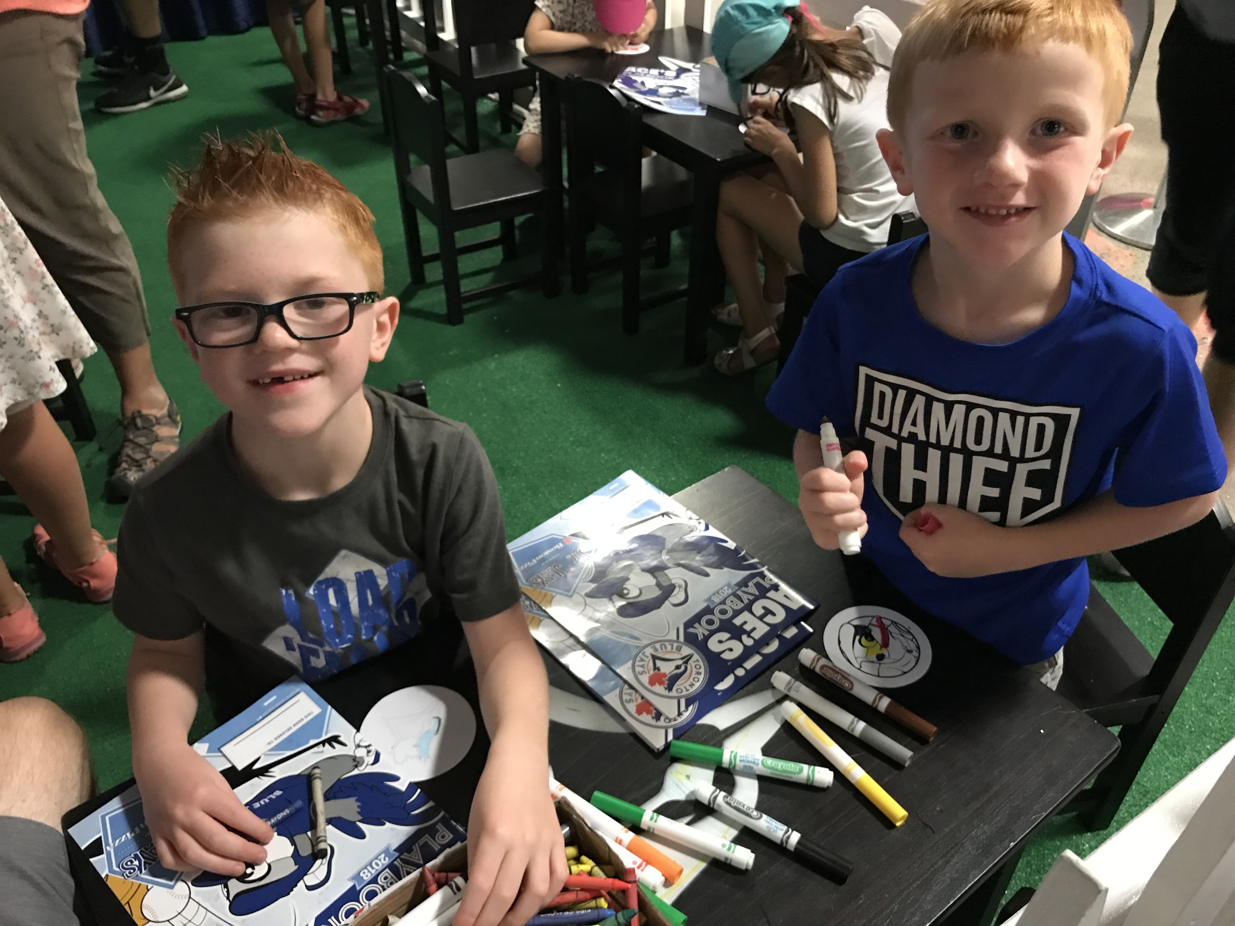 two young boys with coloring books and markers