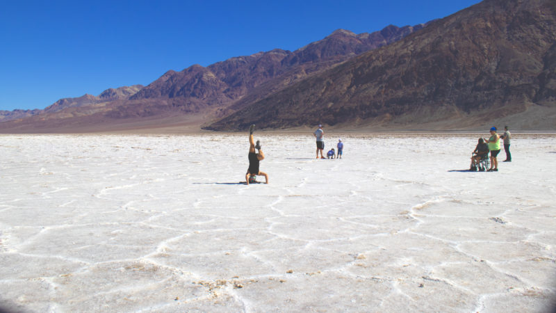 A woman is doing handstands on the salt flats of Badwater Basin
