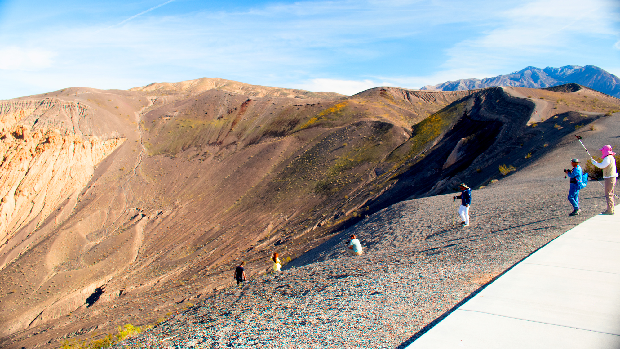 Photo of several tourists slowing climbing down to the crater rim