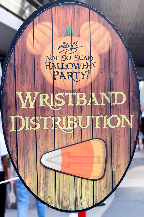 Signs for wristband distribution help party goers get ready for Mickey's Not So Scary Halloween Party.