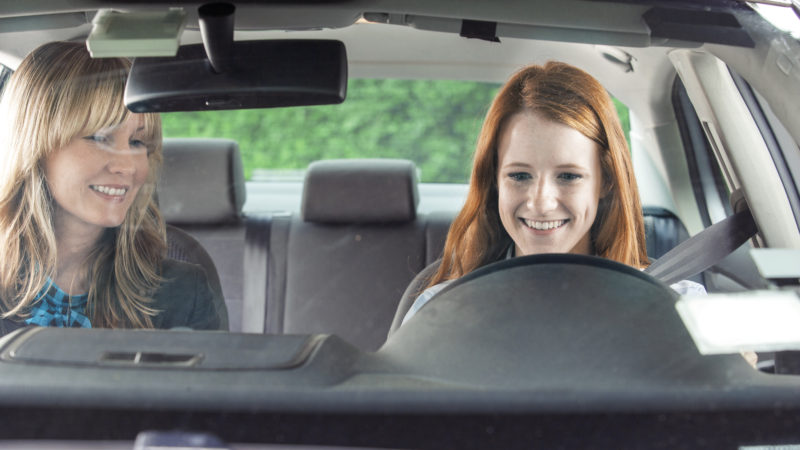 Teen driver in car with adult, using a road trip to help teach teens about new safety tech.
