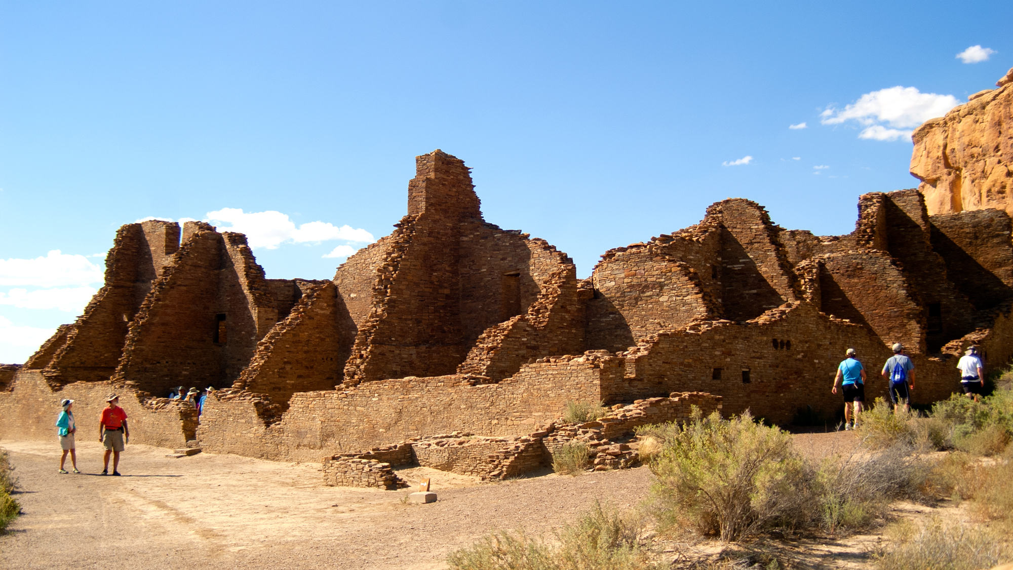 Pueblo Bonito ruins with visitors walking the trail