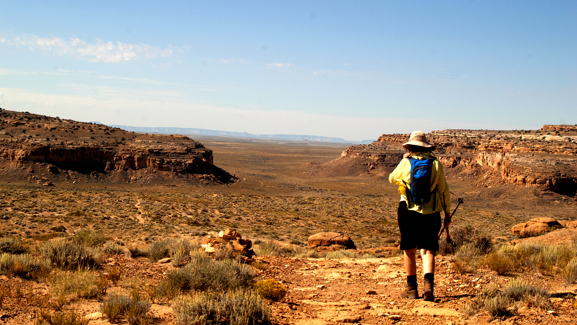 A hiker on the Pueblo Alto trail near the canyon rim.