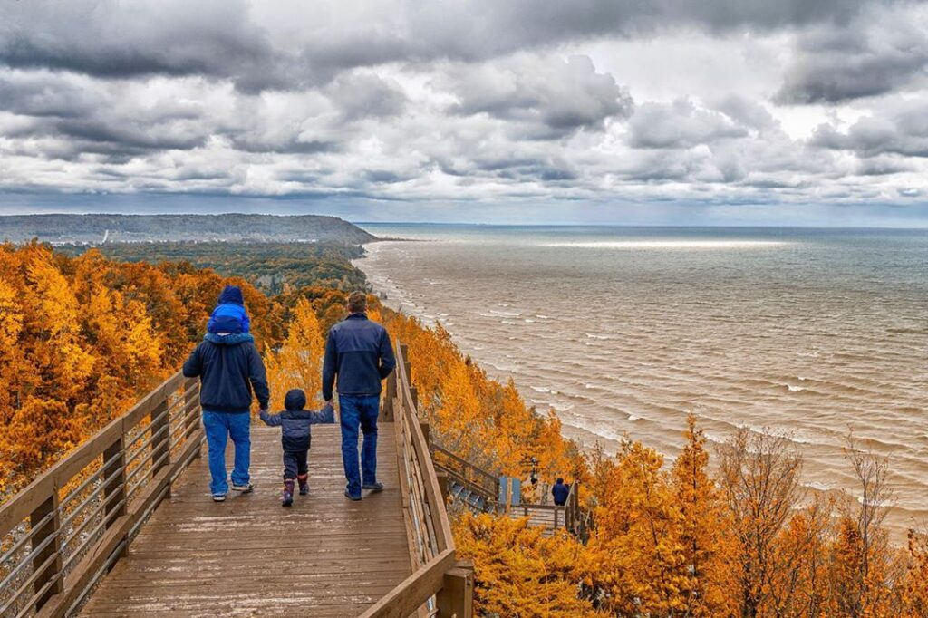 Two dads and two kids walking along a boardwalk overlooking Lake Michigan with trees in fall colors.