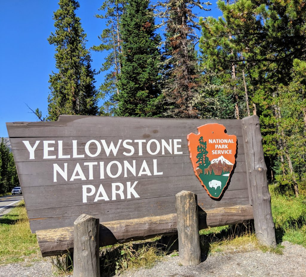 A Yellowstone National Park entrance sign near a visitor center where you need to stop first when visiting the park