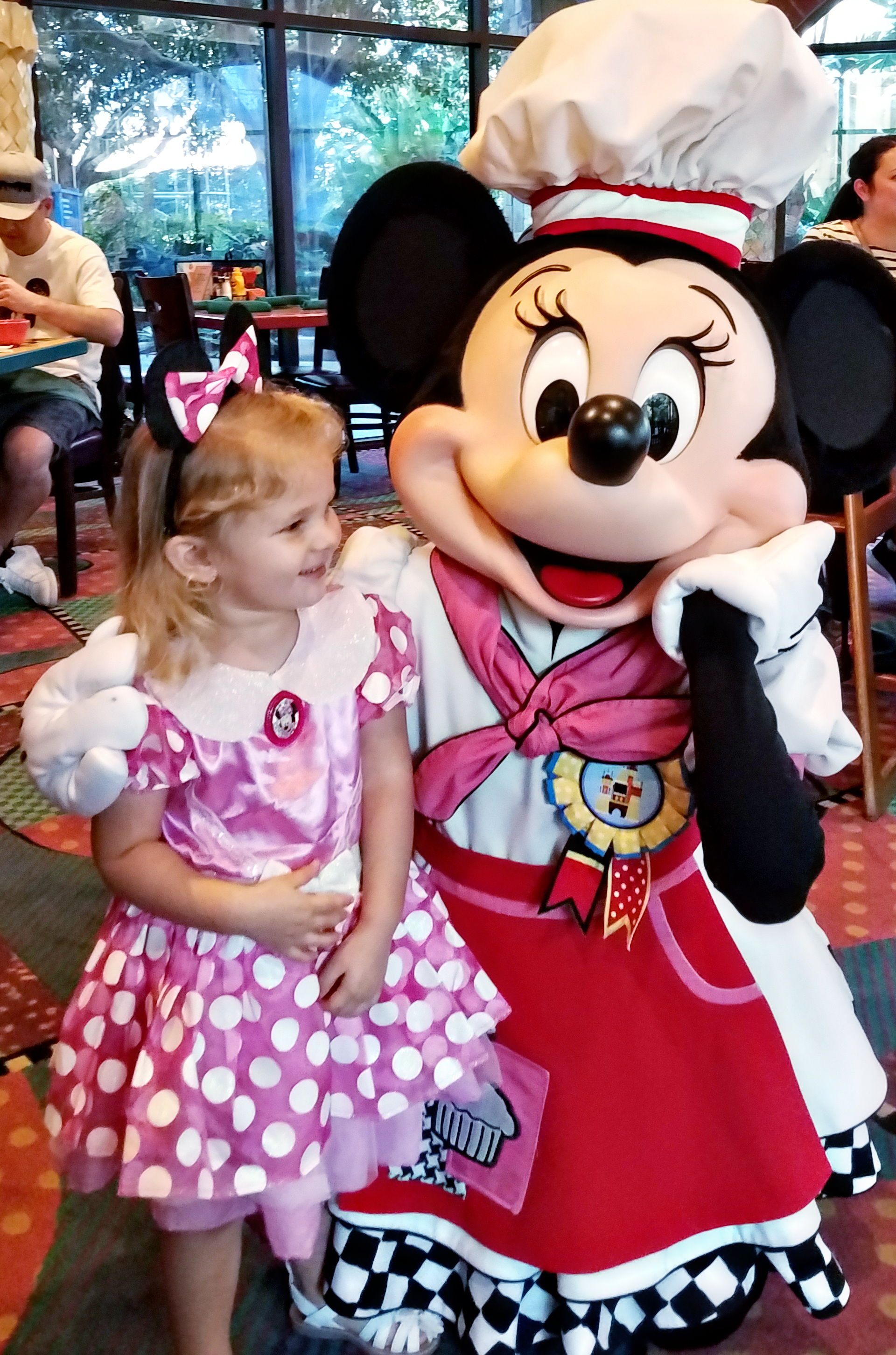 Little girl dressed like Minnie meeting Minnie Mouse at Goofy's Kitchen