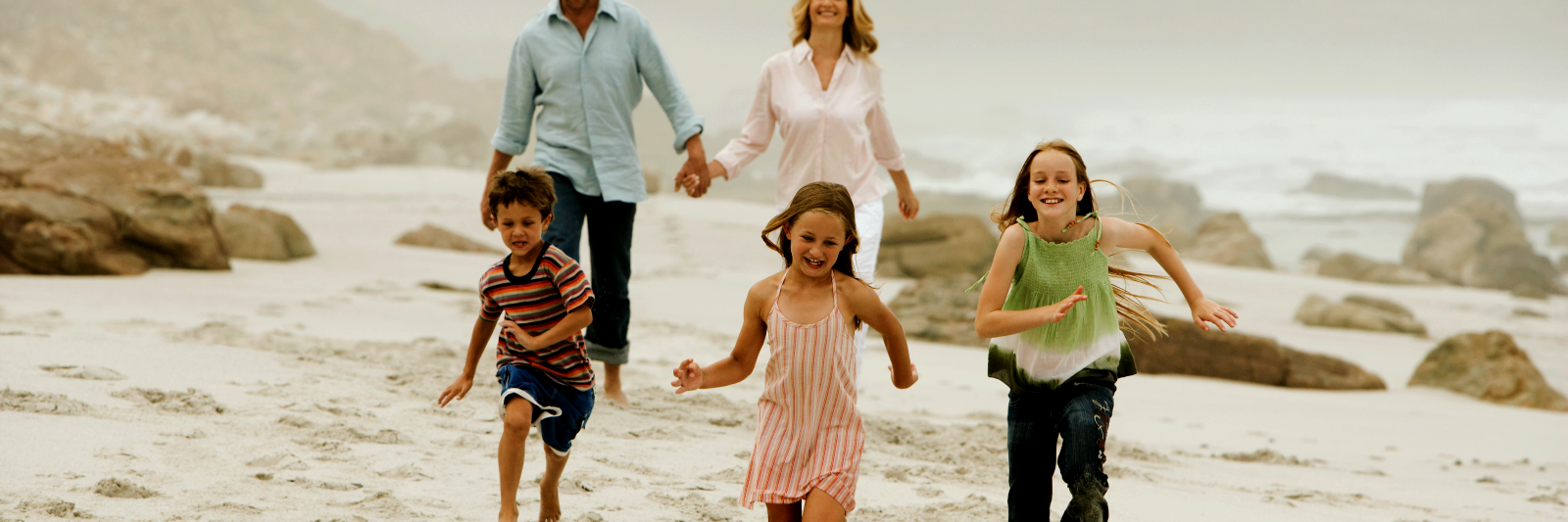 Mom dad and three kids running on beach